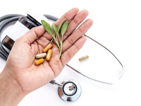 Alternative di assistenza sanitaria a base di erbe fresche e capsula in mano 's medico su sfondo bianco. Archivio Fotografico - 48792724