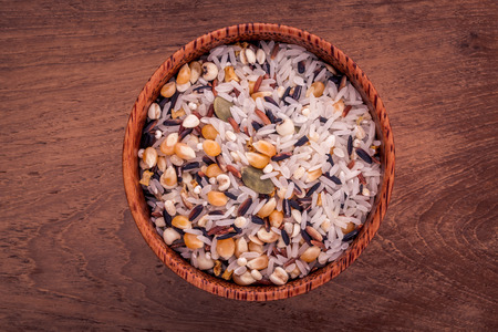 clean food: Mixed Whole grain Traditional Thai rice in the spoon and bowl best rice for healthy and clean food on teak wood background.