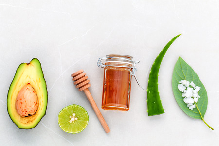 Alternative skin care  and scrub fresh  avocado , leaves ,sea salt , oils, lime and honey on marble background. Фото со стока