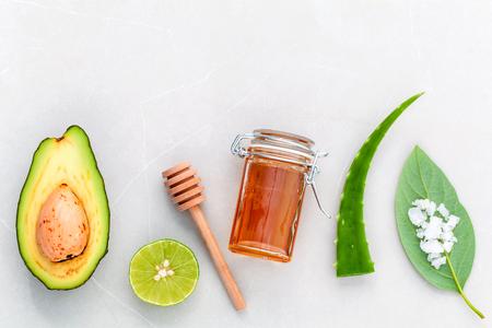 Alternatieve huidverzorging en scrub verse avocado, bladeren, zeezout, oliën, limoen en honing op een marmeren achtergrond. Stockfoto