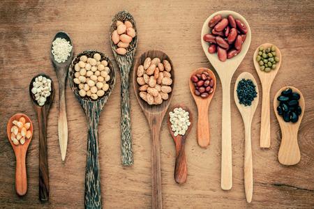 티크 나무 배경에 나무로되는 숟가락에 콩, 렌즈 콩의 구색. 녹두 콩, 땅콩, 콩, 붉은 강낭콩, 검은 콩, 참깨, 옥수수, 팥, 갈색 핀 토 콩. 스톡 콘텐츠