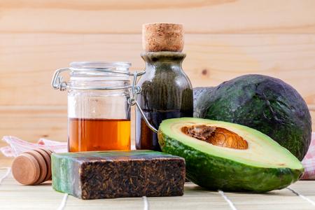 Alternatieve huidverzorging en scrub verse avocado, oliën, honing en avocado zeep op houten achtergrond.