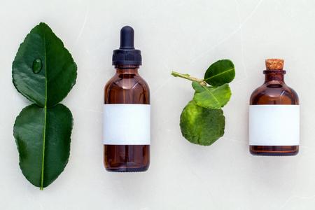 Alternatieve gezondheidszorg verse kaffer llime bladeren en oliën op marmeren achtergrond. Stockfoto