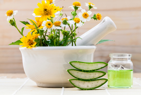 herbal: Alternative health care fresh herbal Aloe vera , oil and wild flower with mortar on wooden background.