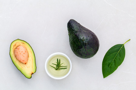 alternative health care: Alternative health care fresh  avocado and leaves on marble background. Stock Photo