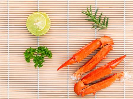 cangrejo: pinzas de cangrejo cocidas con lim�n y perejil en el fondo de bamb�.