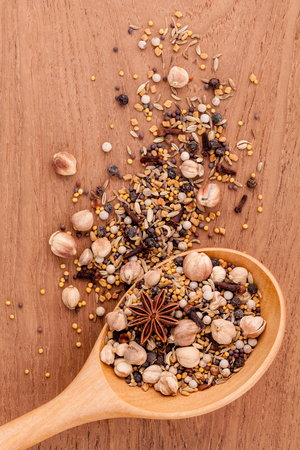 teak wood: Assorted of spices  in wooden spoon  black pepper ,white pepper, black mustard,yellow mustard,fenugreek,cumin and  fennel seeds on teak wood background. Stock Photo