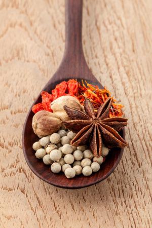 especias: Especias en la cuchara de madera azafrán, vid matrimonio (chino wolfberry), anís estrellado, pimienta blanca con foco superficial sobre fondo de madera de teca.