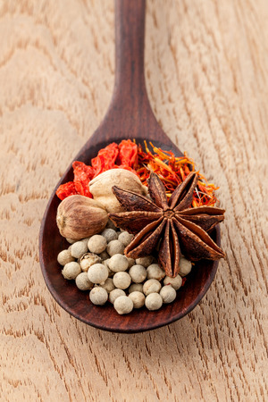 matrimony: Spices in wooden spoon saffron, matrimony vine(chinese wolfberry),star anise ,white pepper with shallow focus on teak wood background.
