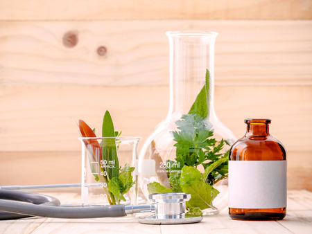 alternative health care: Alternative health care fresh herbal in laboratory glassware  with  stethoscope on wooden background.