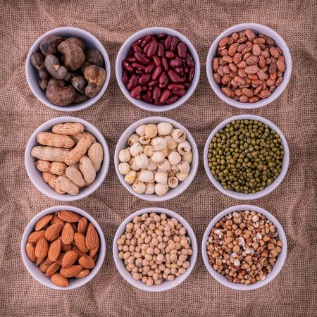 semilla: frijoles, lentejas mixtos y frutos secos en el recipiente blanco sobre fondo marrón paño de saco. frijol mungo, maní, soja, frijol rojo, semillas de loto, almendras, judías verdes, el mijo, el anacardo y judías pintas marrones. Foto de archivo