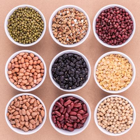 Gemischte Bohnen und Linsen in der weißen Schüssel auf braunem Hintergrund. Mungbohne, Erdnuss, Soja, rote Kidney-Bohnen, schwarze Bohnen, rote Bohnen, grüne Bohnen, Hirse und braune Wachtelbohnen.