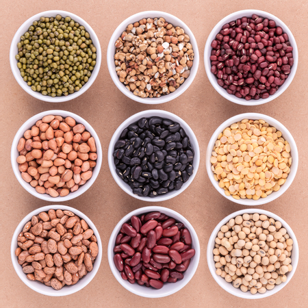 ejotes: granos mixtos y las lentejas en el plato blanco sobre fondo marrón. frijol mungo, maní, soja, frijol rojo, frijol negro, frijol rojo, frijol verde, mijo y frijoles pintos marrones.