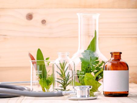 alternative health: Alternative health care fresh herbal in laboratory glassware  with  stethoscope on wooden background.