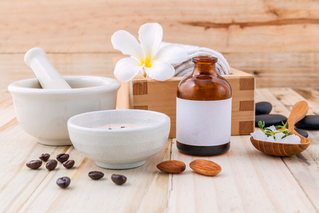 white stones: Natural Spa Ingredients sea salt ,coffee beans ,honey , almonds ,spa stones and white mortar on wooden background for scrub and skin care.