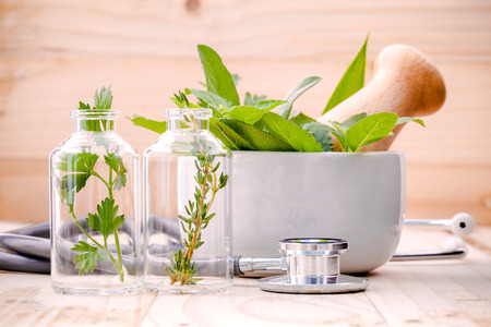 experimento: cuidado de la salud alternativa fresca a base de hierbas en la cristalería de laboratorio con el estetoscopio sobre fondo de madera.