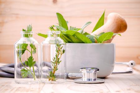 Soins de santé alternatifs à base de plantes fraîches dans la verrerie de laboratoire avec un stéthoscope sur fond de bois.