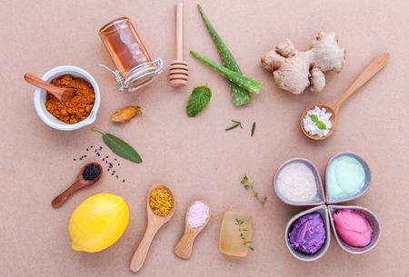 Alternatieve huidverzorging en zelfgemaakte scrubs met natuurlijke ingrediënten salie, kurkuma, zeezout, honing, aloë vera, citroen, rozemarijn, munt en sesam opstelling op bruine lijst.