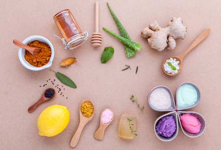 Alternative skin care and homemade scrubs with natural ingredients sage ,turmeric ,sea salt ,honey, aloe vera,lemon ,rosemary,mint and sesame set up on brown table. Stock Photo