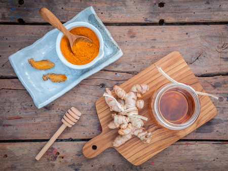 curcumin: Alternative skin care - Homemade scrubs curcumin powder,honey and curcumin roots set up on old wooden table. Stock Photo