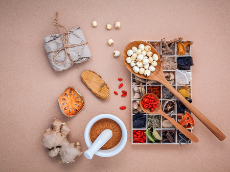 Alternative health care dried various Chinese herbs in wooden box , dried quince ,ginger and lotus seed in wooden spoon with mortar on brown background.