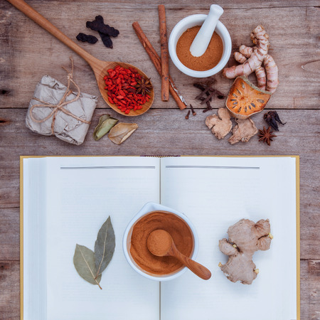 Alternative health care dried various Chinese herbs in  wooden spoon  with mortar on old wooden background.