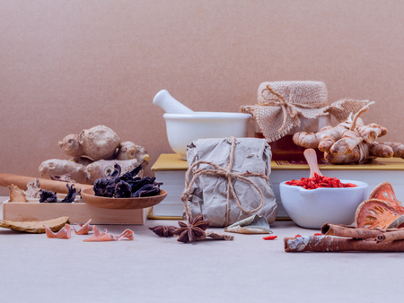 Alternative healthcare dried various Chinese herbs in wooden box and dried roselle in wooden spoon on medical textbook with mortar on brown background.