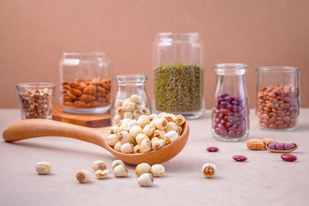 pinto bean: Various beans and nuts in the glass on brown background. mung bean, groundnut, red kidney bean , lotus seed ,almond,millet and brown pinto beans . Stock Photo