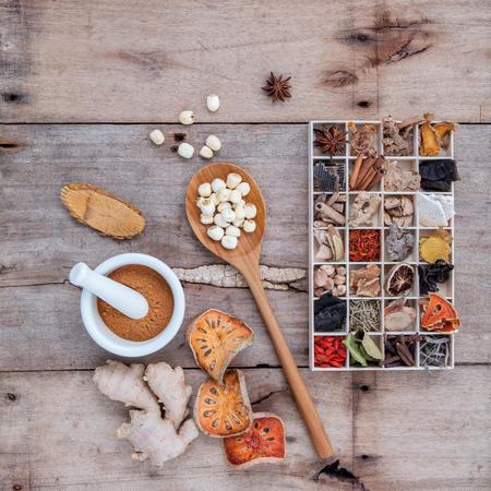 Alternatieve gezondheidszorg gedroogde diverse Chinese kruiden in houten doos en gedroogde kweepeer, gember en lotus zaad in houten lepel met mortel op oude houten achtergrond.