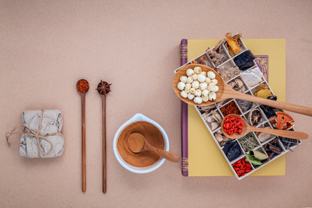 Alternative health care dried various Chinese herbs in wooden box lotus seed and saffron in wooden spoon  on medical textbook with mortar on brown background. 写真素材