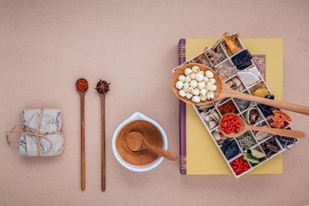 Alternatieve gezondheidszorg gedroogde diverse Chinese kruiden in houten doos lotusbloemzaad en saffraan in houten lepel op medisch handboek met mortel op bruine achtergrond.