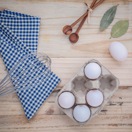 wire whisk: Cardboard egg box with eggs ,pepper bottle ,wooden spoons ,bay leaf and wire whisk set up on old wooden background. Stock Photo