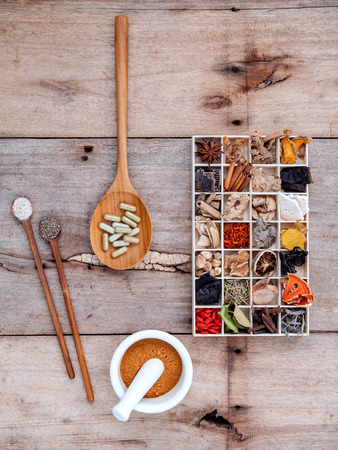 Alternatieve gezondheidszorg gedroogde diverse Chinese kruiden in houten doos en kruiden capsule in houten lepel met mortel op oude houten achtergrond. Stockfoto