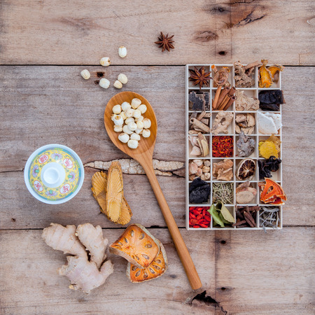 alternative health care: Alternative health care dried various Chinese herbs in wooden box and dried quince ,ginger and lotus seed in wooden spoon with Chinese tea cup on old wooden background.