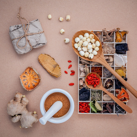 대체 의료 치료 나무 상자, 말린 마 르 멜로, 생강 및 로터스 씨앗 나무 배경에 박격포와 숟가락에에서 다양 한 중국 허브를 건조.