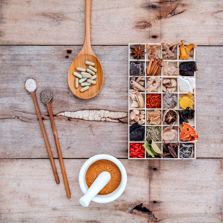 Alternative health care dried various Chinese herbs in wooden box and herbs capsule in wooden spoon with mortar on old wooden background.