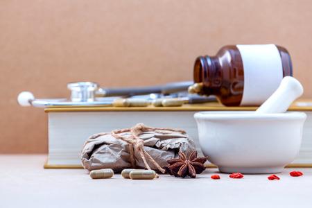 대체 건강 관리 갈색 배경에 흰색 박격포와 허브 캡슐에서 다양 한 중국 약초를 건조. 스타 아니 스에 초점을 필드의 얕은 깊이.