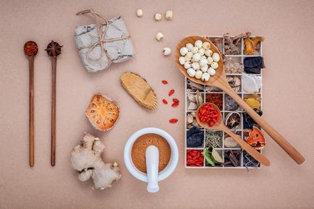 medicina tradicional china: cuidado de la salud alternativa secó varias hierbas chinas en caja de madera, membrillo seco, jengibre y semillas de loto en cuchara de madera con mortero sobre fondo marrón. Foto de archivo