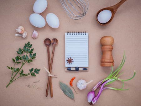 wire whisk: Four white eggs with note book ,pepper bottle ,wooden spoons ,bay leaf parsley and wire whisk set up on brown background. Stock Photo