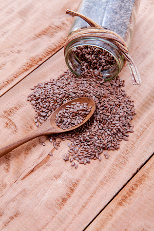 alternative health care: Alternative health care and dieting flax seeds in wooden spoon set up on rustic wooden background. Stock Photo