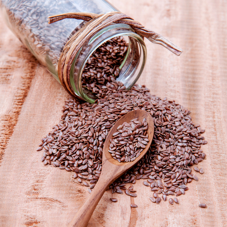 alternative health: Alternative health care and dieting flax seeds in wooden spoon set up on rustic wooden background. Stock Photo