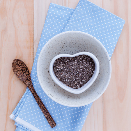 alternative health: Alternative health care and dieting chia seeds in white bowl set up on rustic wooden background.
