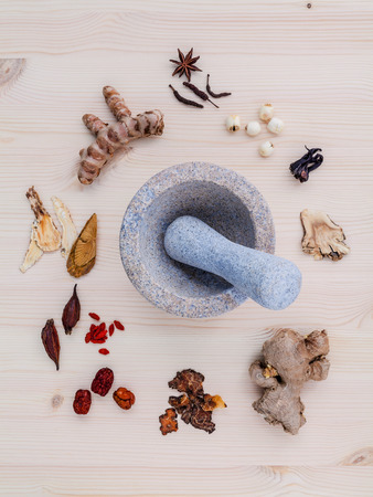 Alternative medicinal dried various Chinese herbs for healthy recipe ginseng ,goji berry ,ginger ,turmeric ,lotus seed ,star anise ,monkey apple and long pepper with mortar on wooden background.