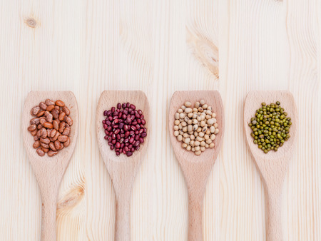 soybean: Assortment of beans and lentils in wooden spoon on wooden background.  soybean, mung bean , red bean and brown pinto beans .