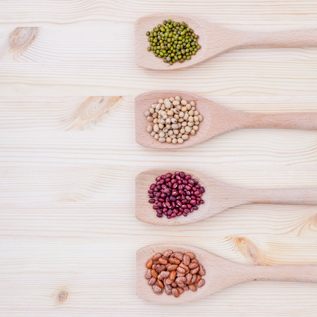 pinto bean: Assortment of beans and lentils in wooden spoon on wooden background.  soybean, mung bean , red bean and brown pinto beans .