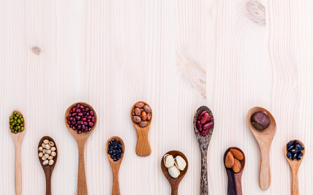 pinto bean: Assortment of beans and lentils in wooden spoon set up on wooden background. mung bean,soybean, red kidney bean , black bean ,red bean ,almonds ,pistachio,chestnut and brown pinto beans . Stock Photo