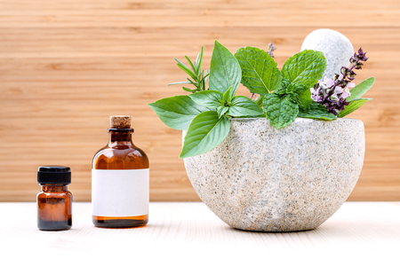 Alternative health care and herbal medicine .Fresh herbs and aromatic oil with mortar and pestle on wooden background. Various herbs rosemary ,sage ,sweet basil leaves and green mint branch. Stock Photo