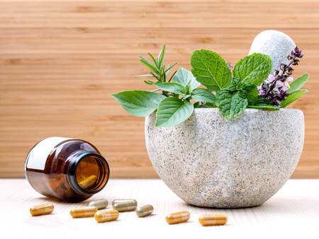 Alternative health care fresh herbs basil ,sage ,rosemary, mint  and herbal capsule with mortar on wooden background.