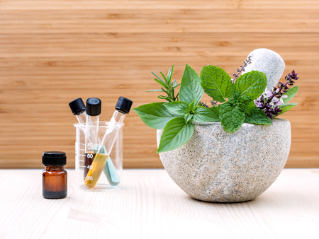 Alternative health care fresh herbs basil ,sage ,rosemary, mint  and essential oil  with mortar on wooden background.