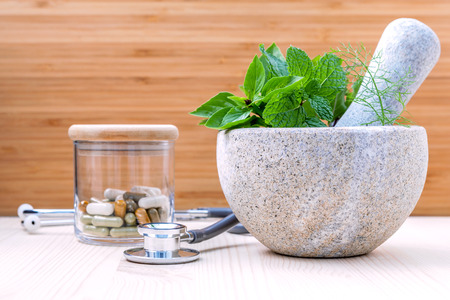 herbal: Fresh herbal leaves basil ,sage , mint ,holy basil ,fennel and capsule of herbal medicine alternative health care with stethoscope setup on wooden background. Stock Photo